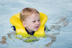 Swimming. Boys in life jacket swims in pool royalty free stock photography
