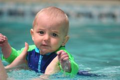 Swimming. Child swimming for the first time in a swimming pool Royalty Free Stock Images