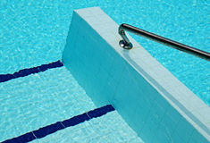 Abstract detail of swimming pool. Hand rail at entrance to a swimming pool with ripples on water surface producing an abstract background royalty free stock photos