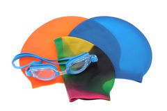 Swimming accessories. Color full swimming caps and blue goggles, isolated on white royalty free stock images