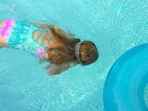 Swimming along. A young girl swimming under the water in a pool Royalty Free Stock Image