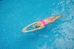 Swimming back crawl stroke. Woman in cap and goggles swimming back crawl stroke royalty free stock images