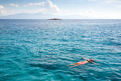 Swimming blue lagoon. The man drift on the ocean waves. The woman on the Aegean Sea. Swimming in a dream. Stock Photos