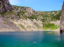 Swimming in the Blue Lake in Croatia. Mother and son swim in the beautiful waters of Blue Lake stock photo