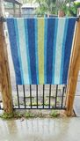 Swimming. Blue stripe towel hanging on home  pool fence Stock Photos