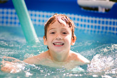 Swimming boy. Young boy swimming in an outdoor pool Royalty Free Stock Image