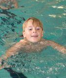 Swimming Boy. Happy boy (7) swimming along in indoor swimming pool Royalty Free Stock Photos