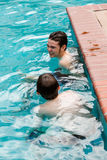 Swimming. Brothers faving fun in outdoor swimming pool on hot summer day Stock Images