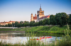 Swimming canoes in Vilnius. Swimming canoes in Neris close old historic buildings in Vilnius, Lithuania royalty free stock images