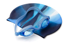 Swimming cap and goggles. Blue swimming cap and goggles isolated on white royalty free stock photo