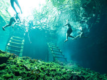 Tourists Swimming in Cenote - Tulum, Mexico. Underwater and swimming in a cenote sinkhole in Yucatan region of Mexico near Tulum stock photo