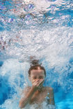 Swimming child jumps underwater in the blue pool with splashes. Funny face portrait of boy swimming and diving in blue pool with fun - jumping deep down Royalty Free Stock Photo
