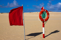 Swimming circle. Life buoy red color on beach with bright sand and sky background. Two warning signs. Safety guard. Lifebuoy, lifeguard, life guard. Vacation stock image