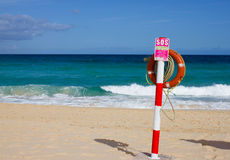Swimming circle. Life buoy red color on beach with bright sand and sky background. Two warning signs. Safety guard. Lifebuoy, lifeguard, life guard. Vacation royalty free stock photo
