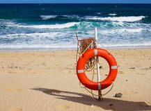 Swimming circle. Life buoy red color on beach with bright sand and sky background. Two warning signs. Safety guard. Lifebuoy, lifeguard, life guard. Vacation stock photo