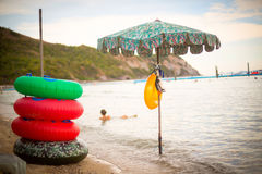 Swimming circle and parasol on seacoast. Blur. Multicolored swimming circle and parasol on seacoast stock image