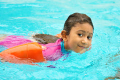 Swimming class. Asian girl in swimmer class with float bands. Indian child learning swimming in pool royalty free stock photography