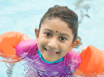 Swimming class. Indian child learning swimming in pool. Asian kid in swimmer class with float bands stock images