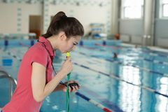 Swimming coach blowing whistle and looking at stopwatch near poolside Royalty Free Stock Images