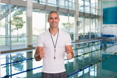 Swimming coach gesturing thumbs up by pool at leisure center Stock Photography