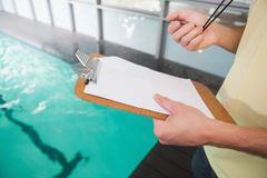 Swimming coach holding stopwatch and clipboard Stock Photos