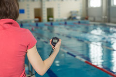 Swimming coach holding stopwatch poolside at the leisure center. Royalty Free Stock Image