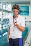 Swimming coach looking at his stopwatch by the pool Royalty Free Stock Photo