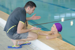 Swimming coach by pool talking to swimmer. Swimming coach by the pool talking to swimmer Stock Images