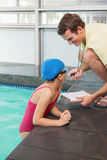 Swimming coach showing time to little girl Stock Photography