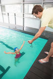 Swimming coach showing time to little girl Royalty Free Stock Image