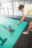 Swimming coach showing time to little girl Stock Image