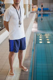 Swimming coach standing by the pool Stock Photography