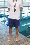 Swimming coach standing by the pool Royalty Free Stock Images