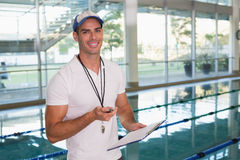 Swimming coach with stopwatch by pool at leisure center Royalty Free Stock Images
