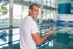 Swimming coach with stopwatch by pool at leisure center Stock Photo