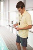 Swimming coach writing on clipboard Royalty Free Stock Photos