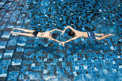 Swimming Couple. A couple swimming in a pool with beautiful design of blue tiles at the floor