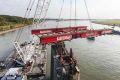 Swimming Crane in action during bridge deconstruction, editorial Royalty Free Stock Image