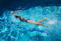 Swimming crawl. Woman with swimsuit swimming on a blue water pool Royalty Free Stock Photography