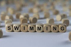Swimming - cube with letters, sign with wooden cubes Stock Photo
