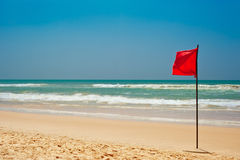 Swimming is dangerous in ocean waves. Red warning flag on beach. Swimming is dangerous in ocean waves. Red warning flag flapping in the wind on beach at stormy Stock Photography
