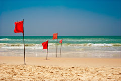 Swimming is dangerous in ocean waves. Red warning flag flapping in the wind on beach at stormy weather Royalty Free Stock Photo