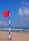 Swimming is dangerous in ocean waves. Red warning flag flapping in the wind on beach at stormy weather. Spain Royalty Free Stock Photo