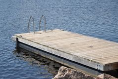 Swimming dock. Floating wooden swimming dock in a sunny day Royalty Free Stock Image
