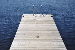 Swimming dock. Floating wooden swimming dock in a sunny day Stock Photos