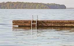 Swimming dock with ladder on a beautiful calm blue lake stock photography