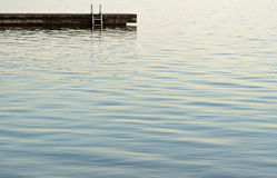 Swimming dock with ladder at the edge of beautiful blue calm watersrs. Swimming dock with ladder at the edge of beautiful calm waters Stock Photos