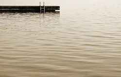 Swimming dock with ladder at the edge of beautiful calm waters Royalty Free Stock Photography