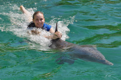 Swimming with a Dolphin !. Woman holding fin and swimming with a dolphin Royalty Free Stock Photography