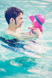 Swimming. Family with cute baby girl faving fun in outdoor swimming pool on hot summer day Royalty Free Stock Images